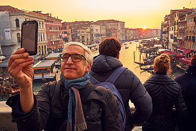 Man takes a selfie on Rialto Bridge in the evening sun - p1312m2082155 by Axel Killian