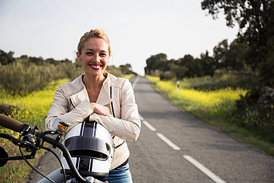 Smiling female biker sitting with helmet on motorcycle - p300m2273459 by Andrés Benitez