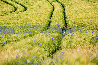 Portrait carefree girl with arms outstretched in sunny, idyllic rural field with wildflowers - p301m2076007 by Sven Hagolani