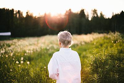 Boy walking through meadow - p312m2091417 by Matilda Holmqvist