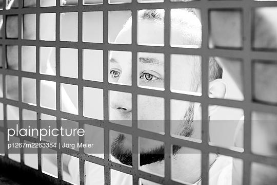 Mann blickt durch ein vergittertes Fenster - p1267m2263384 von Jörg Meier