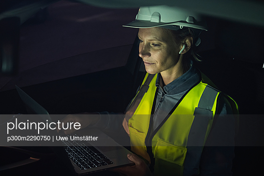Female logistic worker wearing reflective clothing using laptop in car - p300m2290750 by Uwe Umstätter