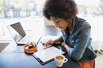 Focused woman working at digital tablet in cafe - p1192m1184116 by Hero Images