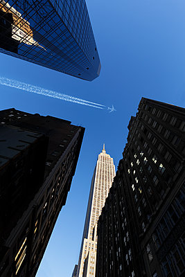 Empire State Building with commercial airliner in the blue sky - p1280m2181945 by Dave Wall