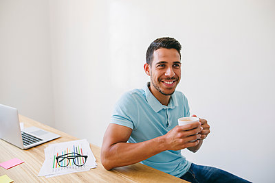Young man in office drinking coffee - p300m1156728 by Bonninstudio