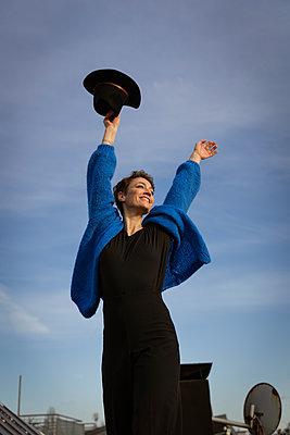 Frau mit Hut steht zufrieden auf Hausdach - p432m2248689 von mia takahara