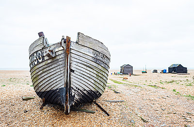 An old fishing boat lies on the beach.with fishermans huts in the background, Dungeness, Kent, England, United Kingdom - p871m2113725 by Paul Porter