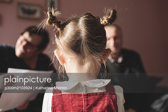 Rear view of girl with braids and grandparents in background - p300m2103924 by Katharina Mikhrin