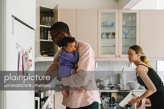 Parents with baby in kitchen - p312m2237478 by Plattform
