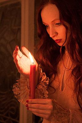 Frau blickt auf Kerze - p045m1208219 von Jasmin Sander