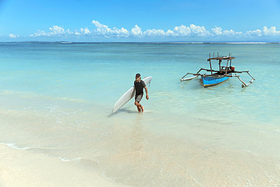 Title Surfer with surfboard at beach - p1166m2141058 by Cavan Images