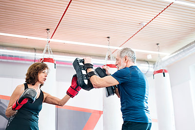 Fit senior woman boxing with her coach - p300m1449407 by HalfPoint