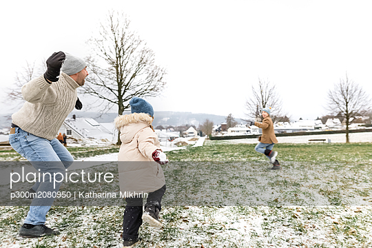 Father and two children having a snowball fight - p300m2080950 by Katharina Mikhrin