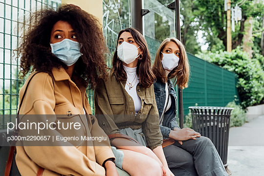 Young women with protective face mask sitting at bus stop - p300m2290657 by Eugenio Marongiu