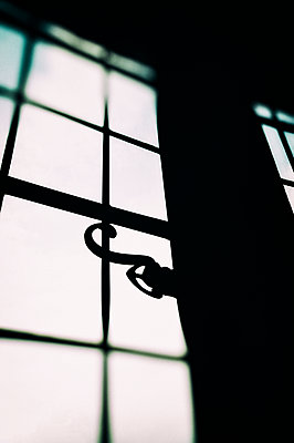 Silhouette of old window and handle from inside building - p1047m2027795 by Sally Mundy