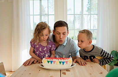 a father with his daughter & son blowing candles on a birthday cake - p1166m2113251 by Cavan Images