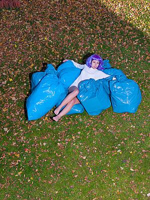 Frau inmitten blauer Müllsäcke - p1279m1092374 von Ulrike Piringer