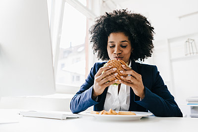 Young businesswoman eating hamburger at her desk - p300m1460069 by Kniel Synnatzschke