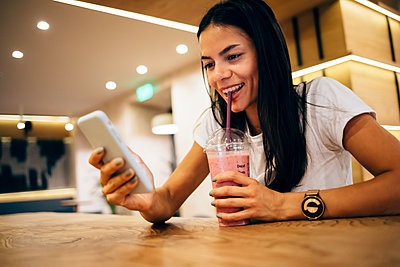 Black-haired woman drinking a smoothie and using smartphone in cafe - p300m2160278 by alev