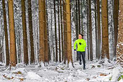 Young woman running on trail in woodland during winter - p300m2256633 by Stefan Schurr