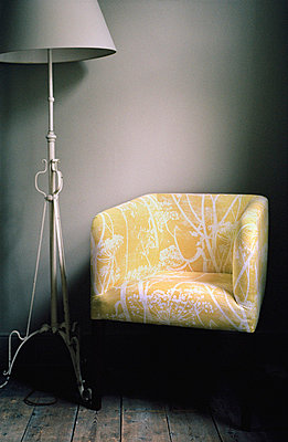 Living room with upholstered armchair and standard lamp - p349m695128 by Emma Lee