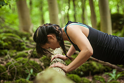 Mid adult woman exercising in forest, doing push-ups on log - p429m1155699 by Colin Hawkins