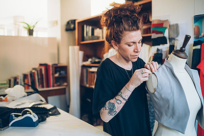 Fashion designer pinning garment onto dressmaker's dummy - p429m2058353 by Eugenio Marongiu