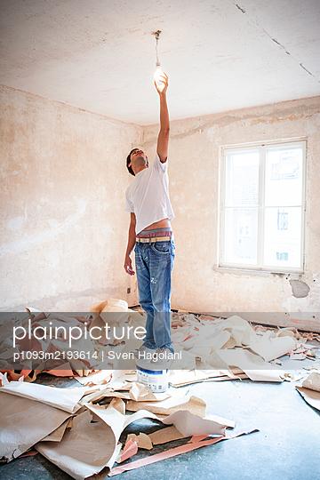 Junger Mann wechselt eine Glühbirne beim Renovieren - p1093m2193614 von Sven Hagolani
