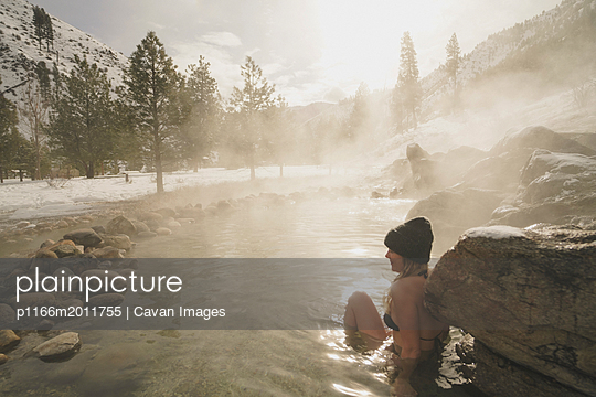 Side view of woman wearing bikini while sitting in thermal pool at forest during winter - p1166m2011755 by Cavan Images