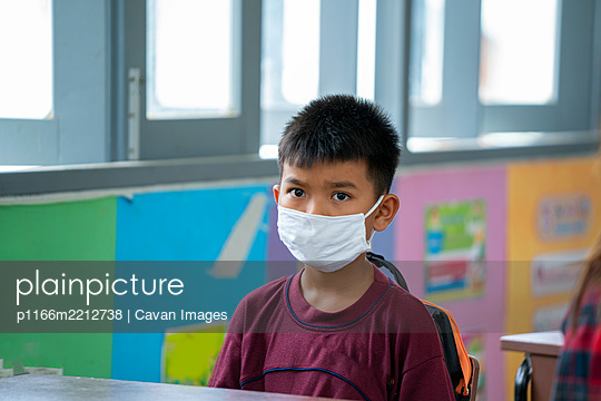 Portrait of an elementary school wearing protective mask to Prot - p1166m2212738 by Cavan Images