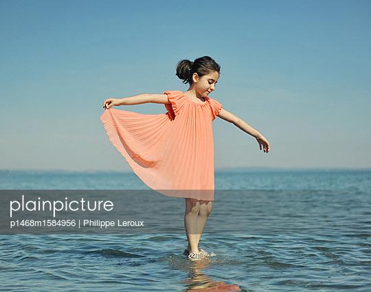 Kleines Mädchen spielt im flachen Wasser - p1468m1584956 von Philippe Leroux