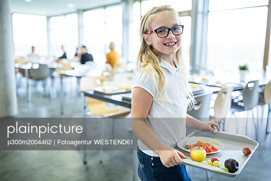 Portrait of smiling schoolgirl carrying tray in school canteen - p300m2004462 von Fotoagentur WESTEND61