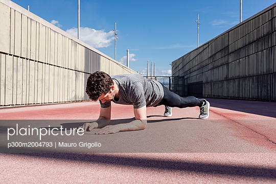 Sportive man exercising outdoors between walls - p300m2004793 von Mauro Grigollo