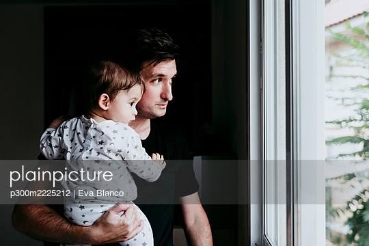 Father carrying son while standing looking through window at home - p300m2225212 by Eva Blanco