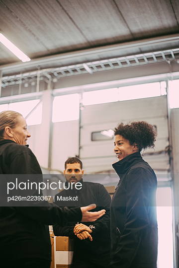 Smiling male and female coworkers discussing in meeting at warehouse - p426m2239367 by Maskot