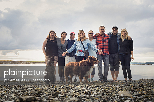 Portrait of adult family and dogs on shingle beach, Maine, USA - p924m1404177 by heshphoto