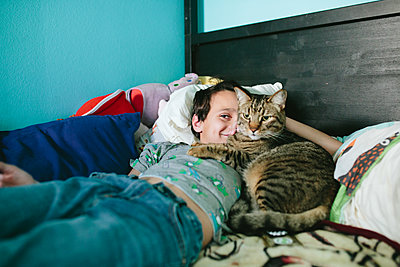 Boy smiles with half of his face blocked by his cat snuggling him - p1166m2201572 by Cavan Images