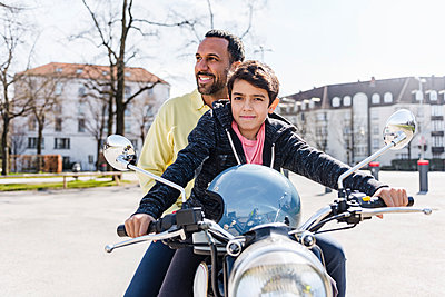 Father and son on a motorbike - p300m1588024 von Daniel Ingold