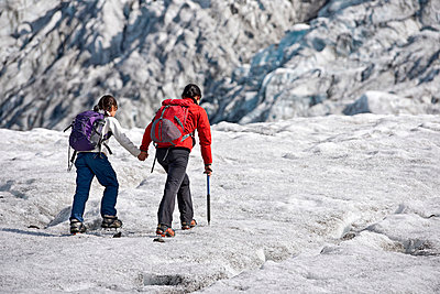 Mother and daughter walking on glacier - p429m727001f by Henn Photography