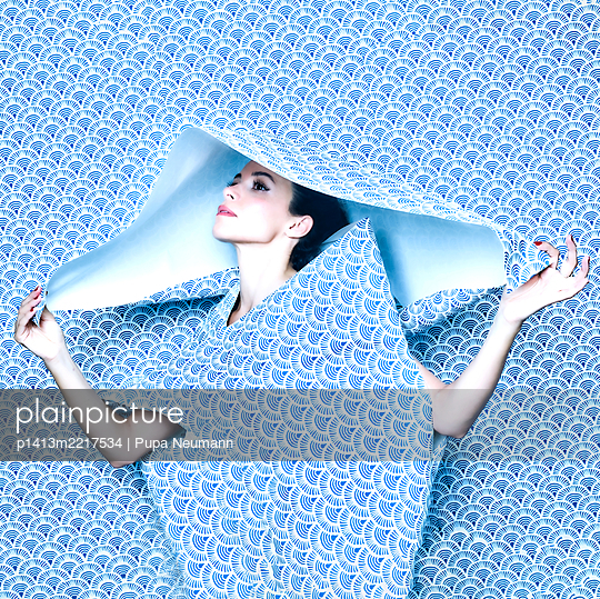 Woman under blue wallpaper, portrait - p1413m2217534 by Pupa Neumann