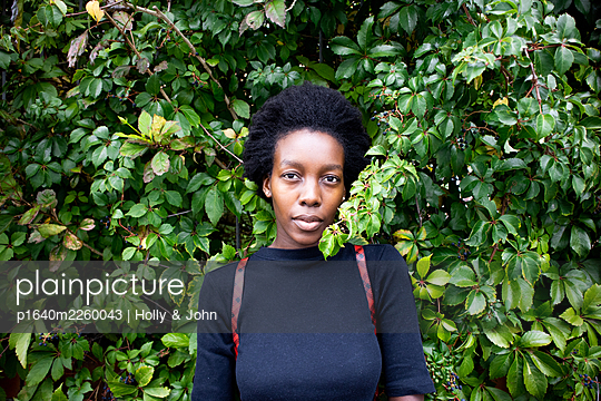 African woman in front of green leaves, portrait - p1640m2260043 by Holly & John