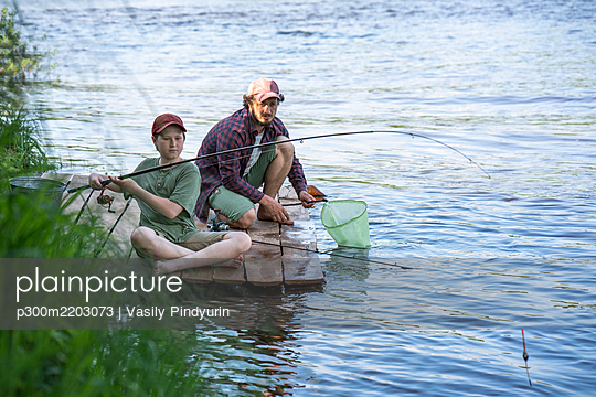 Father and son fishing in river while sitting on boardwalk - p300m2203073 by Vasily Pindyurin
