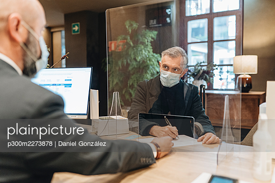 Man wearing protective face mask filling form at hotel reception - p300m2273878 by Daniel González
