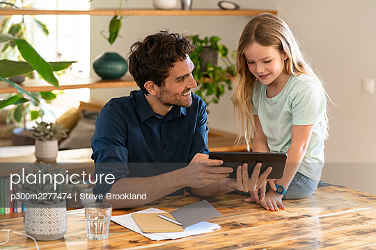 Happy father with digital tablet looking at daughter while discussing at home - p300m2277474 by Steve Brookland