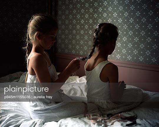 Mädchen hilft Schwester beim Zöpfe flechten - p945m1155036 von aurelia frey