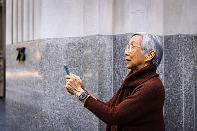 Side view of senior woman using smart phone while standing by wall - p1166m2285620 by Cavan Images