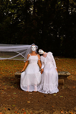 Brides with white masks on a bench in the forest - p1521m2215017 by Charlotte Zobel