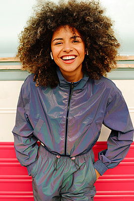 Portrait of happy stylish young woman wearing tracksuit outdoors - p300m2179983 by Lightsy Studio