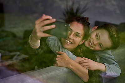 Mother taking selfie with son while relaxing on sofa at home seen through window - p300m2197376 by Stefanie Aumiller
