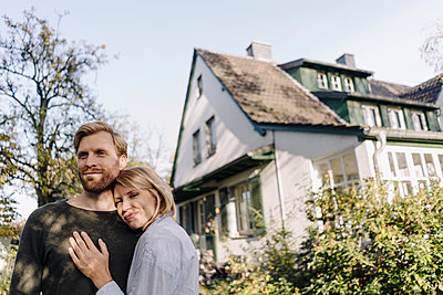 Smiling affectionate couple in garden of their home - p300m2205525 by Kniel Synnatzschke
